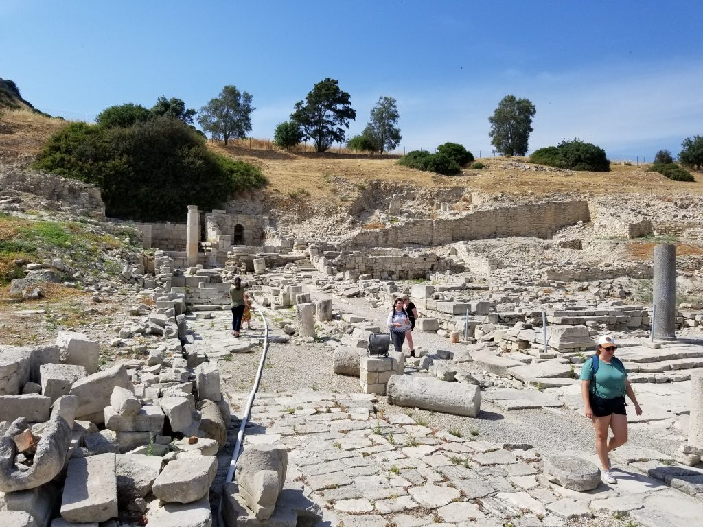 Several people walk through ancient ruins, including standing columns