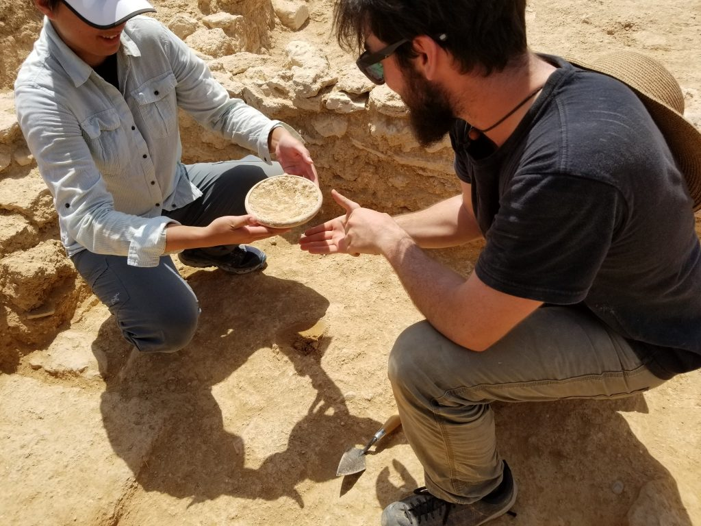 Two archaeologists carefully remove an intact bowl